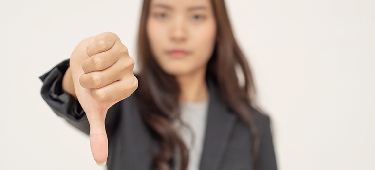 Woman holding a thumbs down