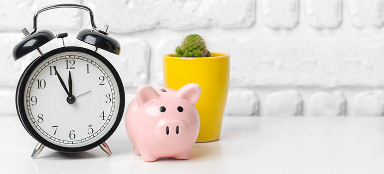 Clock, piggy bank, and office plant