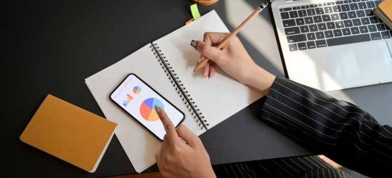 Person looking at charts on phone and taking notes.