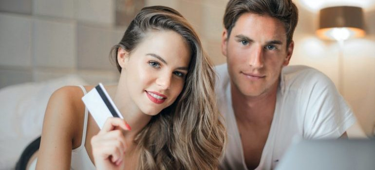 Young couple with a laptop and credit card.