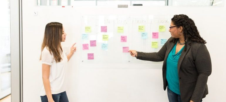Two women in front of a whiteboard, discussing dealing with negative customer reviews.
