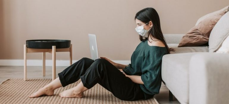 Woman sitting with her laptop, with a protective mask.
