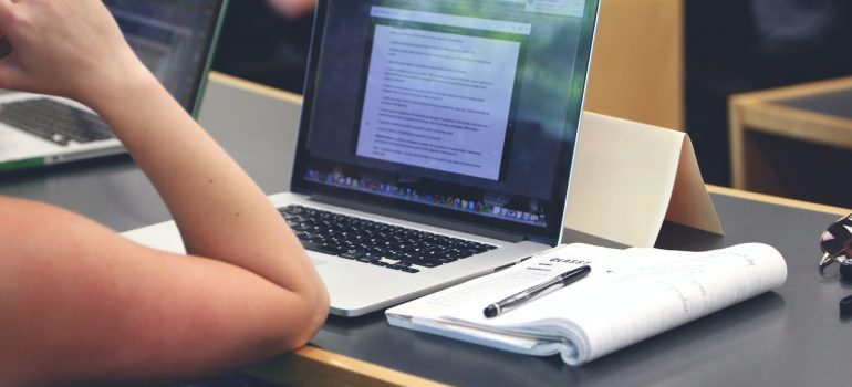 Image of a person writing on a laptop and taking notes.