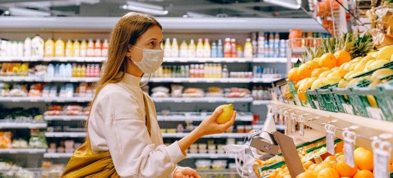 Woman with mask in a supermarket, buying fruit