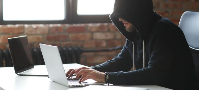 Person with a black hoodie, using a laptop