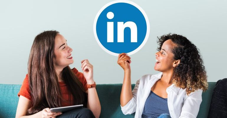 Two women on a couch, holding the LinkedIn logo