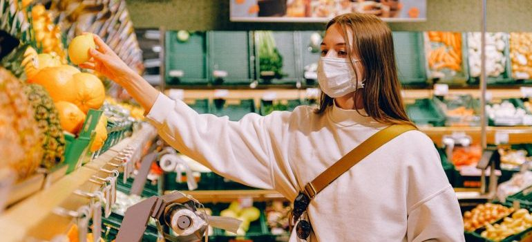 a girl wearing a face maske shopping for groceries