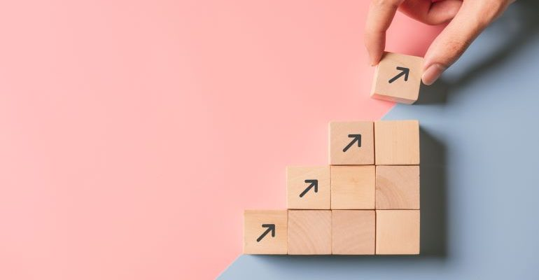 Wooden cubes with arrows to symbolize growth