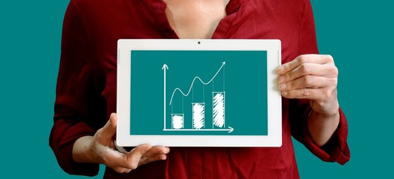 A woman holding a tablet that shows an upward graph.
