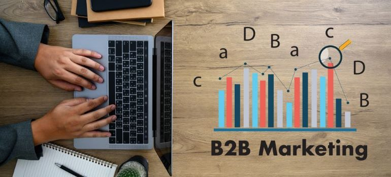 B2B marketing under a stats illustration, next to a laptop on a wooden table.