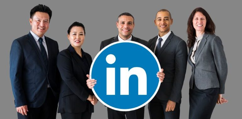 A team of business people, holding the LinkedIn logo sign.