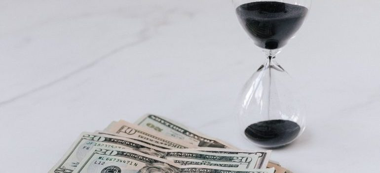 An hourglass with black sand next to US dollar bills.