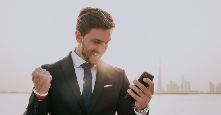 Businessman looking at his phone with excitement.