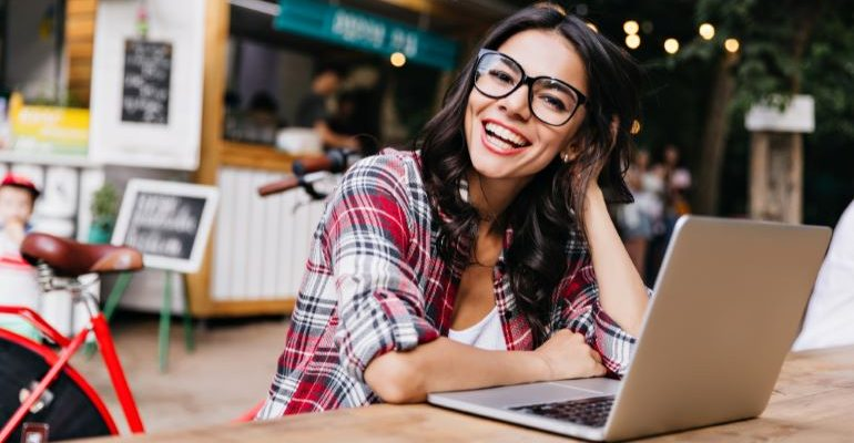 Girl with laptop, smiling.
