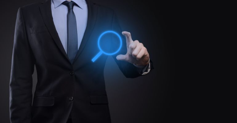 Businessman holding a blue magnifying glass icon.