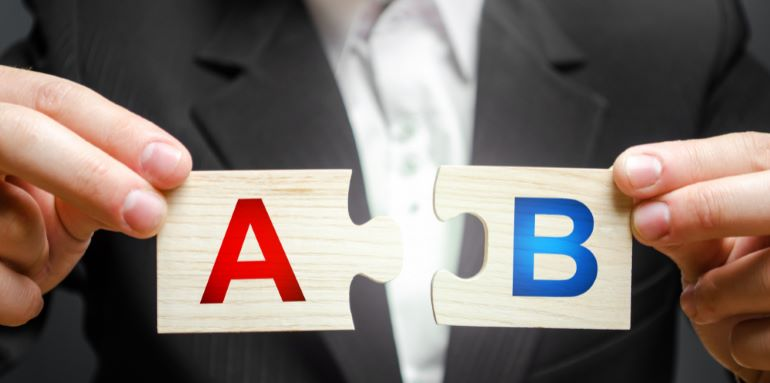 Businessman holding two puzzle pieces marked with A and B.