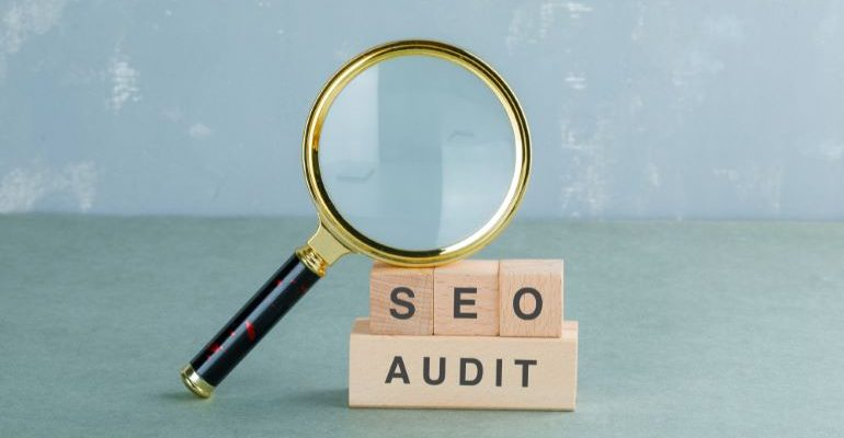 Magnifying glass leaning on SEO AUDIT spelled out with wooden cubes.