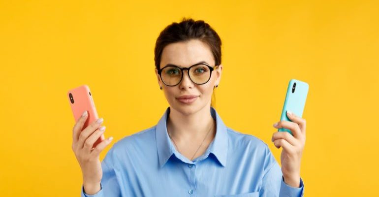 Woman holding two phones.