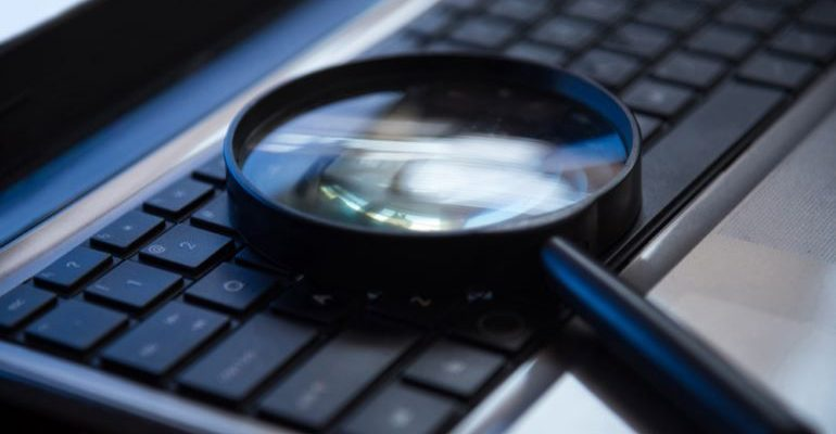 A magnifying glass on a keyboard.